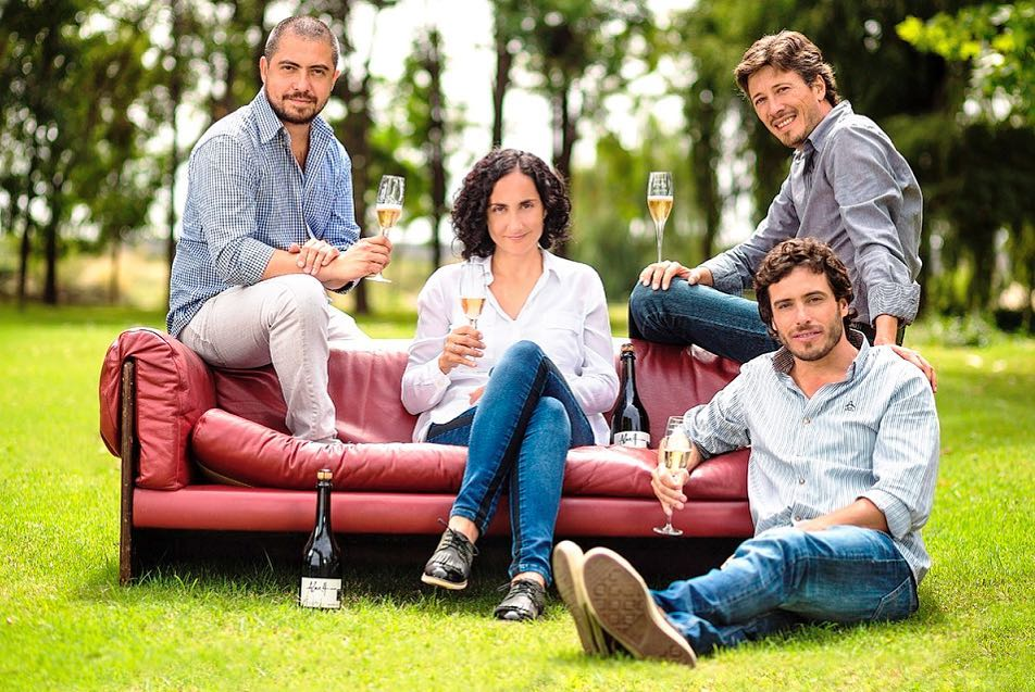 Four founders of Alma Cuatro wines posing on a couch outside toasting with champagne glasses